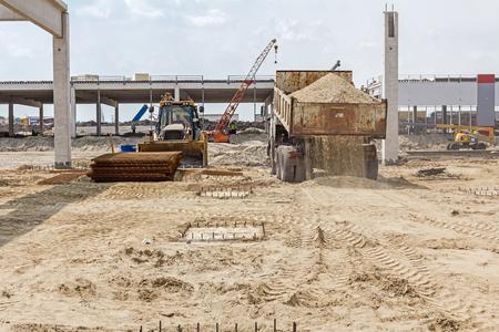 unloading: Dumper truck is unloading soil or sand at construction site. Landscape transform into urban area.