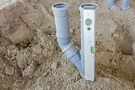 Placing set of new plastic sewer pipes into the ground assembled and lined up on building site. Stock Photo