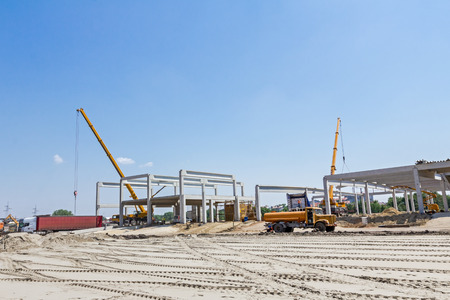 Mobile crane is carry concrete joist to assembly huge hall. Landscape transform into urban area with machinery, people are working. View on construction site.