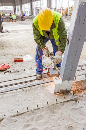 cut through: Metalworker is increasing holes diameter using metal torch. Worker is using acetylene torch to cut through metal in metalwork.