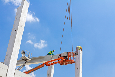 rigger: Mobile crane is operating and worker is assembly concrete joist in high place. Height worker is placing truss on building skeleton. Stock Photo