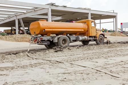 Yellow vintage Tankwagen wird auf der Baustelle geparkt. Landschaft verwandeln sich in Stadtgebiet.