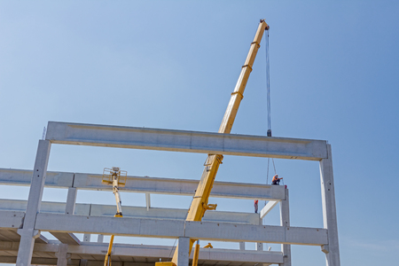 risky job: Height worker is high up on concrete frame without proper safety equipment.