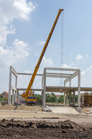 joist: Mobile crane is carry concrete joist to assembly huge hall. Landscape transform into urban area with machinery, people are working. View on construction site.