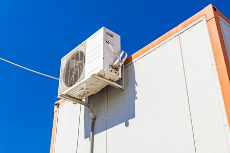 backstop: Outdoor unit, compressor, of air conditioner is placed on white container office.