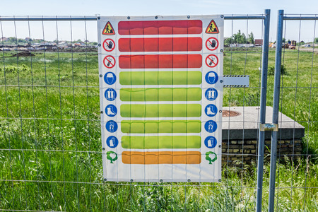 fastened: Safety list of behavior rules on a construction site. Building site safety rules are on the poster fastened to the fence. Stock Photo