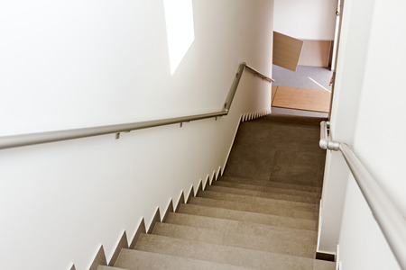 Stairway with metallic banister in a new modern building. Every building is required to have emergency stairways as safety measure.