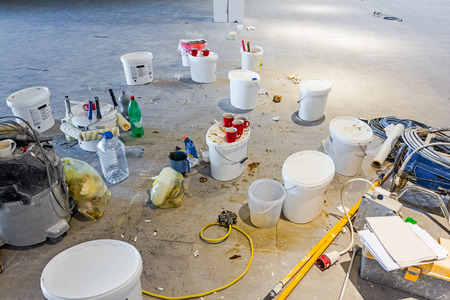 After pause workers have left messy leftovers on building site, painting cans.