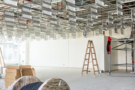 I lavoratori sono usati scala di legno per completare soffitto dell'ufficio sospesi in cantiere.