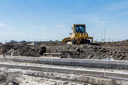 earthmover: Construction site, the roadside stones are lined and placed on gravel. Earthmover with caterpillar is moving earth in background.