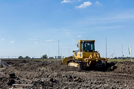 earthmover: Earthmover with caterpillar is moving earth outdoors.