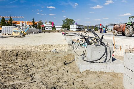 cornerstone: Bunch of various electric cables are coming out from foundation made of concrete. Stock Photo