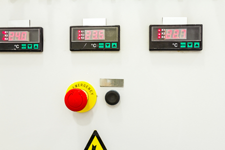 override: Electrical control panel containing has a digital temperature gauge with warning sticker and an emergency shutdown (panic) button.