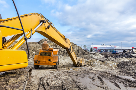 mini loader: View on excavator with caterpillar who is parked at construction site.