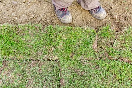 zapatos de seguridad: Trabajador en calzado de seguridad está de pie sobre césped nuevo jardín en un sitio de construcción residencial.