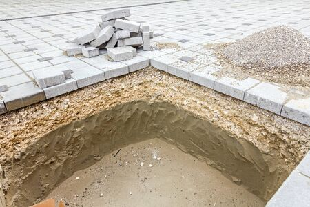 dug: Dug hole in urban settlement for tree, to be planted Stock Photo