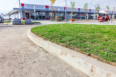 sod: Unrolling laying sod for new lawn at parking lot at shopping mall.