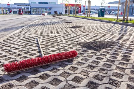 a pile: Urban space is swept with a wide red broom. Piles of dirt are lined up. Stock Photo