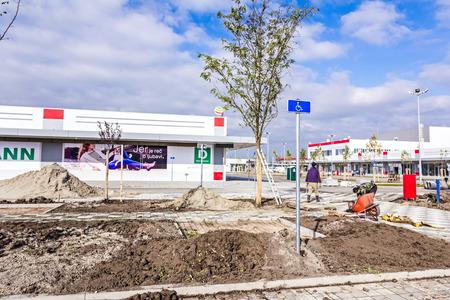 """sembrando un arbol: Zrenjanin, Vojvodina, Serbia - 09 de octubre de 2015: trabajadores del Jard�n est�n plantando un �rbol en el nuevo centro comercial """"AVIV Park"""" Editorial"""