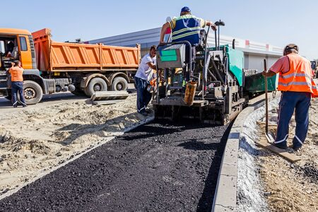 construction crew: Hot asphalt is applied to the ground by construction crew with tarmac road laying machine. Editorial