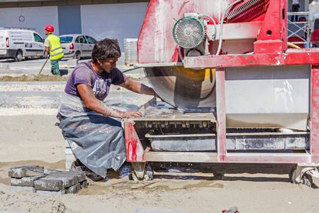rotates: Zrenjanin, Vojvodina, Serbia - September 14, 2015: Worker using abrasive action to slice through concrete brick as the blade rotates at high speed. Editorial