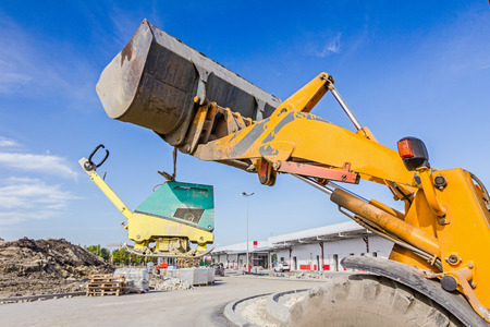 vibration machine: Excavator is moving over building site with raised up front bucket, vibration plate compactor machine is hanging.
