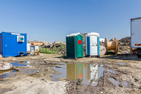 The group of transportable public street toilet is placed at building site. Stok Fotoğraf