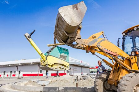 compactor: Excavator is moving over building site with raised up front bucket, vibration plate compactor machine is hanging.