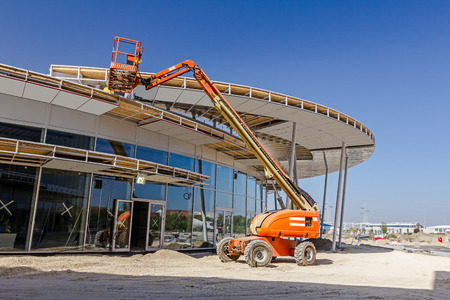 Zrenjanin, Vojvodina, Serbia - September 14, 2015: High elevated cherry picker people are working at new assembled canopies on construction site.