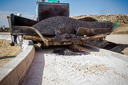 paver: Front view on asphalt laying machine full of fresh asphalt at road construction site. Hot asphalt is spreading from paver machine on prepared ground.