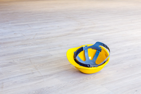 Yellow construction, industrial helmet on floor made of laminate with wooden color.