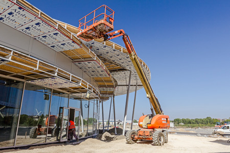 canopies: Zrenjanin, Vojvodina, Serbia - September 14, 2015: High elevated cherry picker people are working at new assembled canopies on construction site.