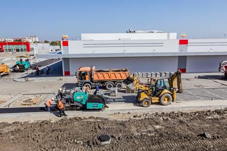 blacktop: Zrenjanin, Vojvodina, Serbia - September 14, 2015: Excavator in his lifted bucked is transporting asphalt at construction site.