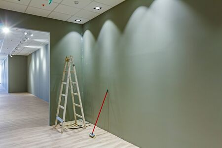 air duct: Workers are used wooden ladder to complete modern office ceiling with air duct and lamps.