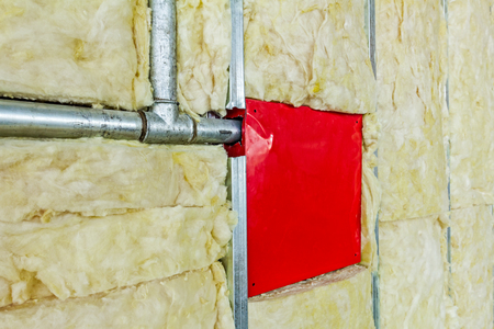 rock wool: Back side of fire box with symbol for hydrant is in unfinished party wall. Stock Photo