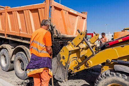 dumper truck: Zrenjanin, Vojvodina, Serbia - September 14, 2015: Dumper truck is unloading asphalt in excavator range at construction site.