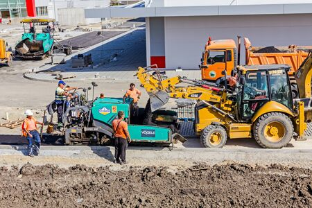 dumper: Zrenjanin, Vojvodina, Serbia - September 14, 2015: Excavator with his lifted bucked is transporting asphalt from dumper truck to decanting into tarmac road laying machine at construction site.