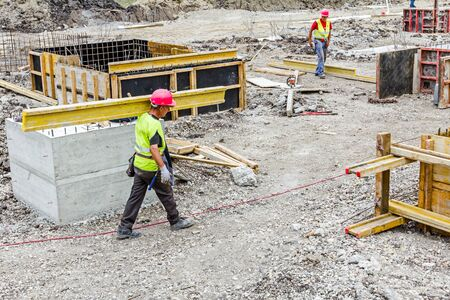 transferred: View on team of construction workers who are transfer mold components for assembling over building site.