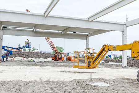 rigger: High elevated cherry picker with rigger on construction site. Editorial