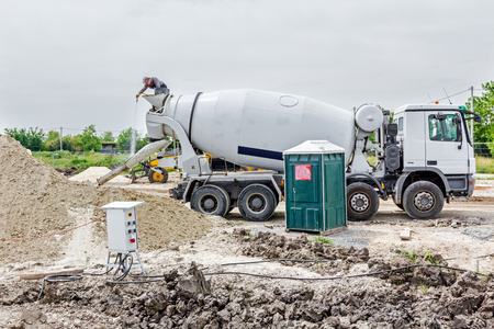 water jet: Driver is washing mixer truck with water jet, after concrete casting.