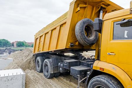 dumper: Dumper truck is unloading soil or sand at construction site. Landscape transform into urban area.