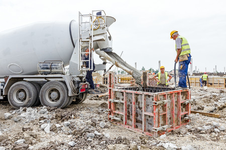 concrete structure: Zrenjanin, Vojvodina, Serbia - May 21, 2015: Workers at building site are pouring concrete in mold from mixer truck.