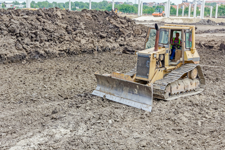 earthmover: View on bulldozer while he moving, leveling ground at building site.