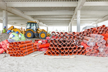 construction materials: Sewer pipes waiting to be placed into the ditch at construction site.
