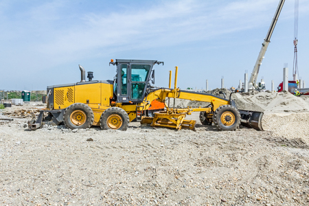 Grader is parked on gravel on construction site. Landscape transform into urban area with machinery, people are working.