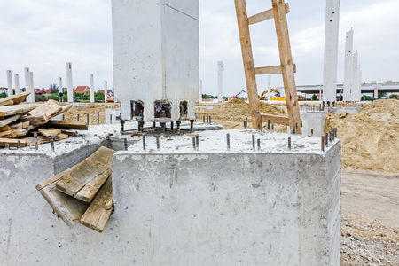 protruding: Workers are used wooden ladder at construction site. Reinforced steel bars are protruding from the concrete pillar, base for new edifice.