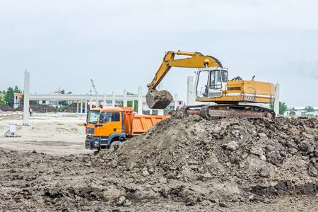 manage transportation: Yellow excavator is filling a dump truck with soil at construction site, project in progress.