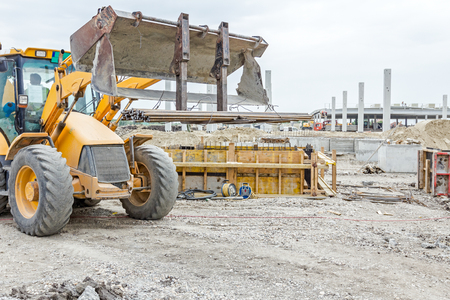 special steel: Excavator with inserted forklift is loaded with metal bars for concrete reinforcement.