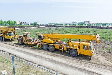 camion grua: Rodillo de camino amarillo con espigas para la compactación del suelo con dos grúas sobre camión móviles está estacionado en frente del sitio de construcción.