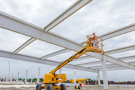 High elevated cherry picker with rigger on construction site. Standard-Bild